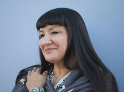 Sandra Cisneros looks off to the left standing against a blue background