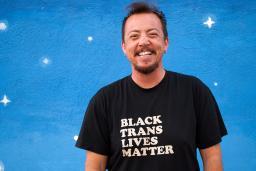 "TC Tolbert smiles, wearing a ""Black Trans Lives Matter"" shirt, standing against a blue wall"