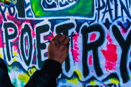 """""""POETRY"""" spray painted on a wall, being touched up with a paintbrush"""