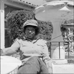 Poet Rita Dove wears a hat and sits by a fountain outside the University of Arizona Poetry Center in Tucson, Arizona.