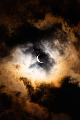 A crescent moon in the cloudy sky