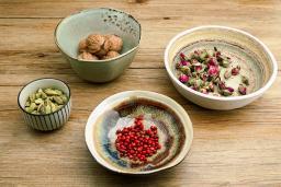 ceramic bowls of ingredients including cardamom, nutmeg, and rosebuds