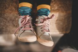 Kids wears pink shoes with blue and yellow socks / photo by Zan