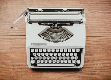 Gray typewriter on a wooden table