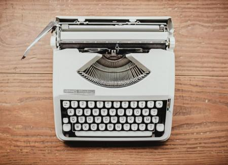 Gray typewriter on a wooden background / photo by Bernard Hermant