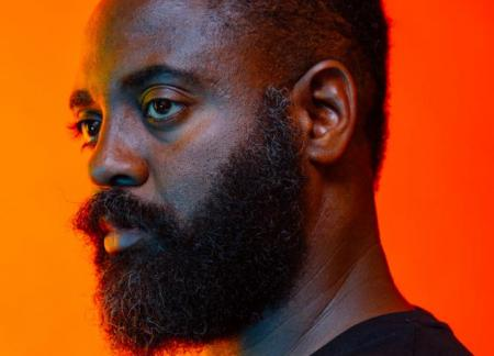 Reginald Dwayne Betts looks to the left agains a glowing orange background