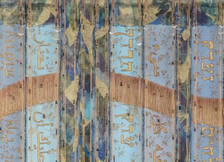 Textile art with calligraphy in Greek, Arabic, and Hebrew.