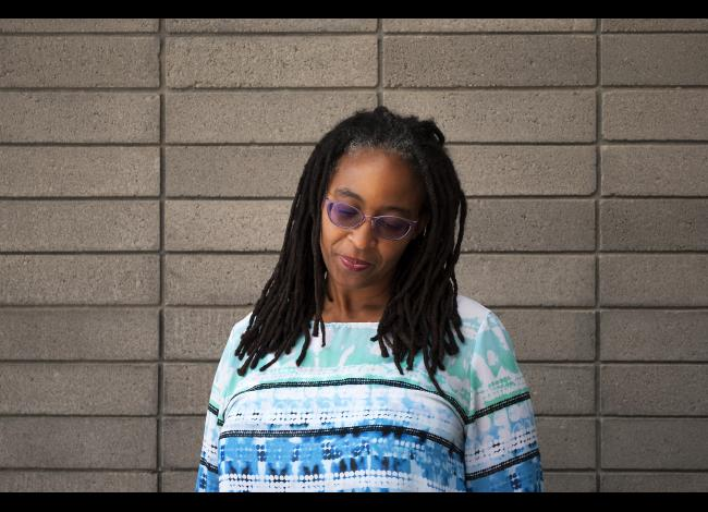 Camille T. Dungy stands in front of a gray brick wall, head tilted downward, slightly smiling