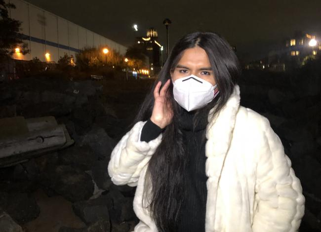 A brown trans woman stands by rocks at night. She is wearing black & a white coat. She is masked and putting her hair behind her ear. In the background are blurry lights from buildings.
