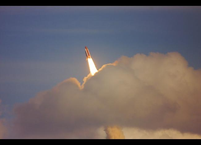 a space shuttle launches with smoke and clouds surrounding it as it ascends