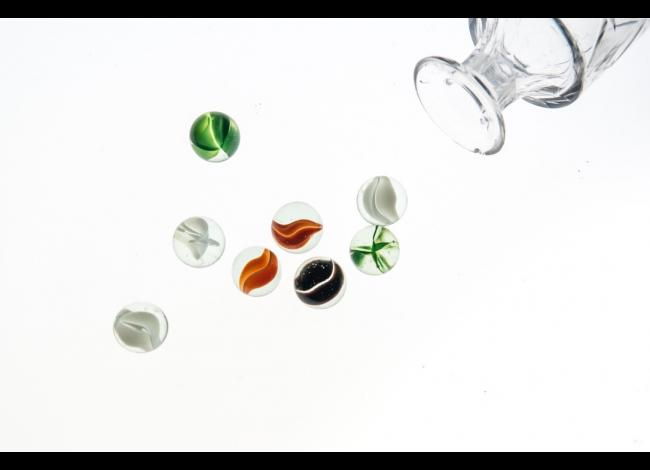 Marbles and glass jar on white background