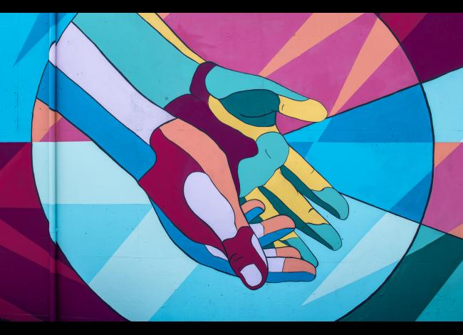 A mural of extended hands in maroon, bright blue, aqua, and yellow.
