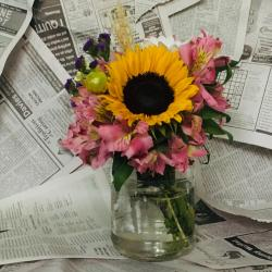 sunflower bouquet in a vase against a newspaper background
