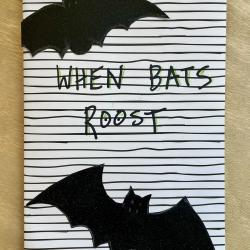 """Cut out bats on lined cover with the text, """"When bats roost."""" Created by Gema Ornelas."""