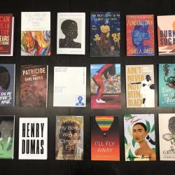 Eighteen colorful books of poetry arranged on a brown wooden table.