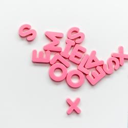 Pink magnetic letters on a white fridge