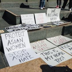 Anti-Asian hate protest signs laid out on grey steps.