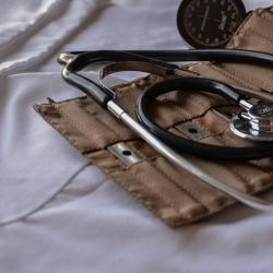 Stethoscope on bag with medical tools, laying on white sheet