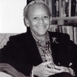 The poet sits in front of a bookshelf in a black blazer
