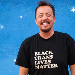 """A white person with short hair and a beard stands in front of a blue background in a shirt that reads """"Black Trans Lives Matter"""""""