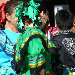 Kids with their backs turned to the camera in baile folklorico dress / photo by Delia Wagner
